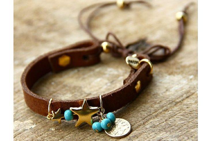 Bruine Lederen Armband Goudkleurige Ster & Muntje | Deze bruine lederen armband is voorzien van goudkleurige studs, een grote en kleine goudleurige ster, een muntje, het Bazou embleem en turquoise details. De armband kan worden gesloten d.m.v. een strik of een knoopje.  #bazou #bracelet #armband #leer #star #coin #rendezvousofstyle