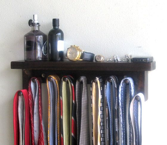 This is a Tie rack made from wood. The tie is made with a shelf to hold watches, colognes and other accessories. The tie rack has 9 pegs. The rack