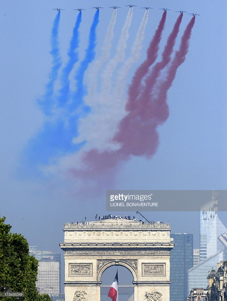Nine alphajets from the French Air Force Patrouille de France releasing trails of red, white and blue smoke, colors of French national flag, fly over the Arc de Triomphe during the Bastille Day parade on the Champs Elysees avenue, on July 14, 2013 in Paris.