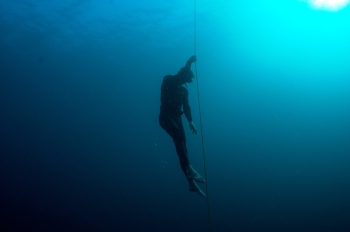 A rope is used to help descending to the deep blue. Freediving in Amed, Bali.