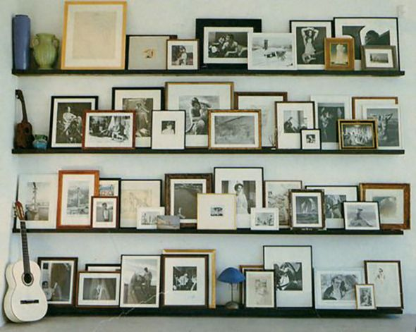 gallery wall with picture ledges and mixed black white and stained wood frames white mats and black and white photos