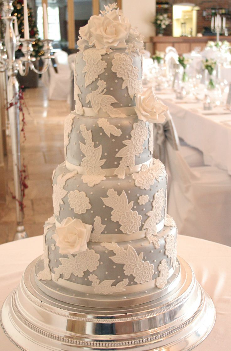 This four tier Wedding cake design featured a silver metallic background with white lace decoration. Handmade white sugar roses completed this dramatic look.