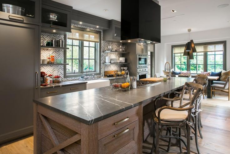 A mix of contemporary style and country charm brings this spacious, eat-in kitchen to life. Charcoal gray cabinets and gray stone countertops blend seamlessly together, while a gray and white chevron tile backsplash breaks up the monochromatic space. The large island pairs with country-style barstools to provide additional seating for dining.