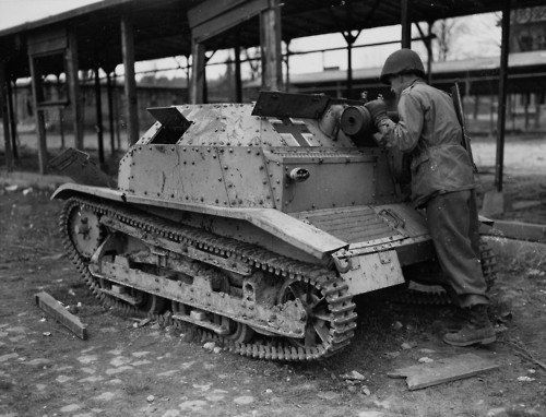 A Polish TKS tankette is inspected by an American soldier, France 1945