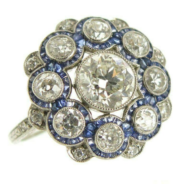 Circa 1920s Platinum Ring, centrally set with a .95 carat European cut Diamond and surrounded by another 1.10 carat of European cut Diamonds and Caliber cut Sapphires. The Diamonds are very clean and face up fairly white. The ring is further enhanced with