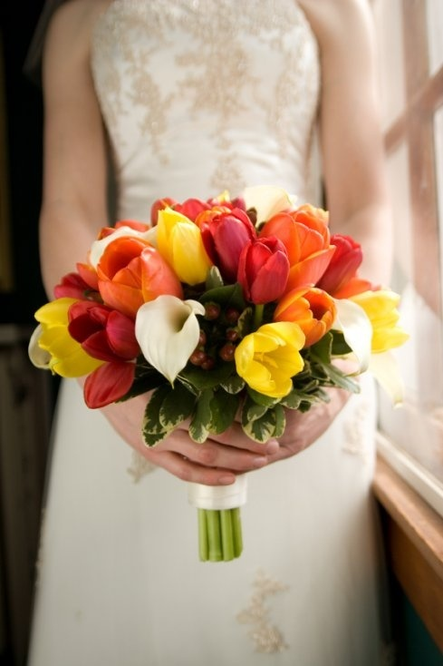 Warm colored tulips with white cala-lilies create stunning bouquet.