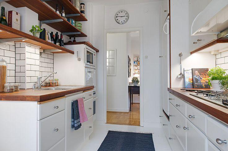 W tej niedużej kuchni smacznie skomponowano białe meble z ciemnobrązowym drewnem blatu i półek. Półkami zastąpiono szafki na jednej ze ścian, dzięki czemu zabudowa wygląda lżej. Wyrazistym elementem wykończenia ścian jest biała cegiełka z czarną fugą, która nawiązuje do stylu retro.