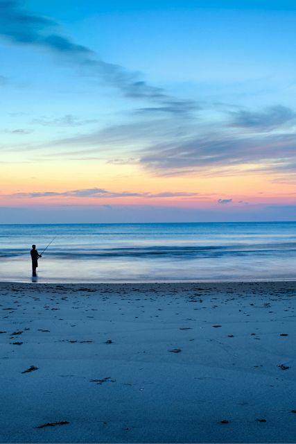 Corolla, North Carolina, United States - man fishing on beach shore