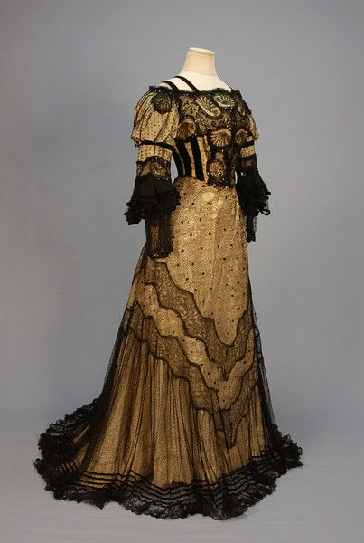 TRAINED BLACK LACE EVENING GOWN with SEQUINS, c. 1905. 2-piece dotted net with lace insertions and velvet trim over cream silk faille: Boned square neck front closing bodice with puffed shoulder, ruffled 3/4 sleeve decorated with sequins, velvet bands and shell pattern lace. Skirt with two wavy bands of floral lace, ruffled hem with velvet bands.
