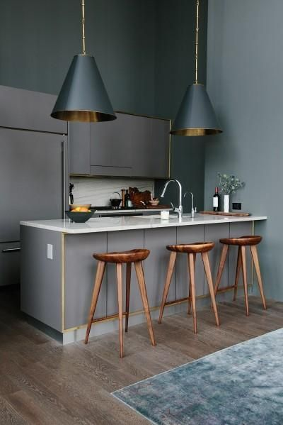 Modern kitchen well designed with white carrara countertops and backsplash, wood chair, grey cabinets and black stylish lights