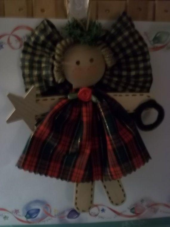 Este ángel lindo está hecha de palitos de madera grande. Su vestido se hizo de calico pelo es rizado yute. Un arco de la cinta de papel para las alas y holly sale de su halo. Medidas de 7, no incluyendo suspensión.