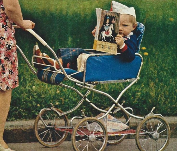 The delights of puppetry engross a tot in his stroller (Moscow, Russia) National Geographic | January 1978