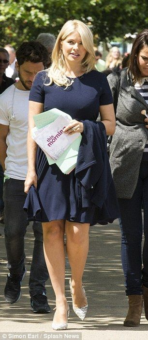 Walking tall: The 33-year-old linked arms with a colleague as she walked down the bank in her Asos number
