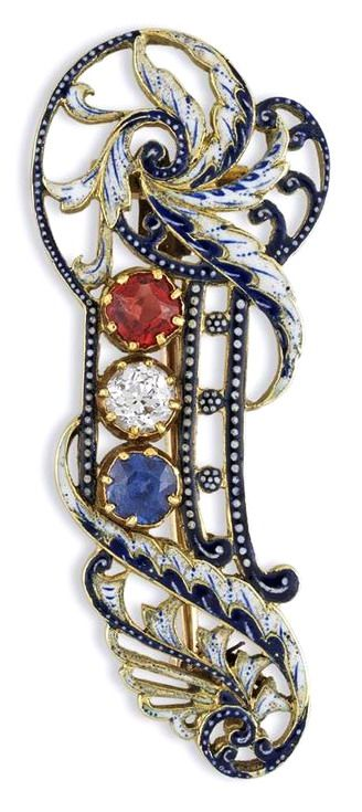 A SAPPHIRE, RUBY, DIAMOND AND ENAMEL BROOCH BY GIULIANO  A sapphire, ruby, diamond and enamel brooch by Giuliano, with a central round brilliant-cut diamond, flanked by a round faceted ruby to one side and a round faceted sapphire to the other, all gems set within a decorative scrolled openwork blue and white enamel frame, overall measurements approximately 37 x 15 mm, circa 1860, gross weight 5.6 grams, slight restoration to enamel.