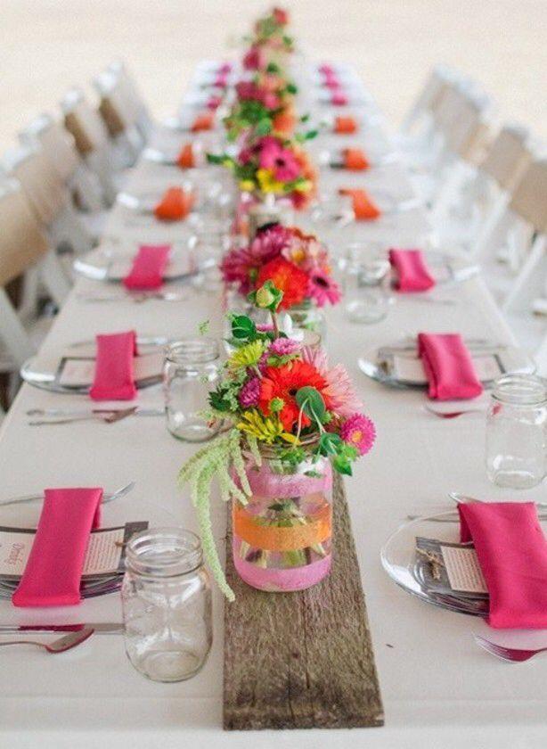 Gebruik kleine glaasjes als vazen en zet over de hele lengte van de tafel vrolijke bloemen neer
