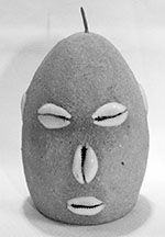 A fetish head representing Eleggua, the Santeria Orisha of doorways and crossroads. These effigies are made of items sacred to Eleggua, with cowries for facial features. They are most commonly placed behind or near doors for protection, or kept on altars to receive offerings (ebo) made to the Orisha.
