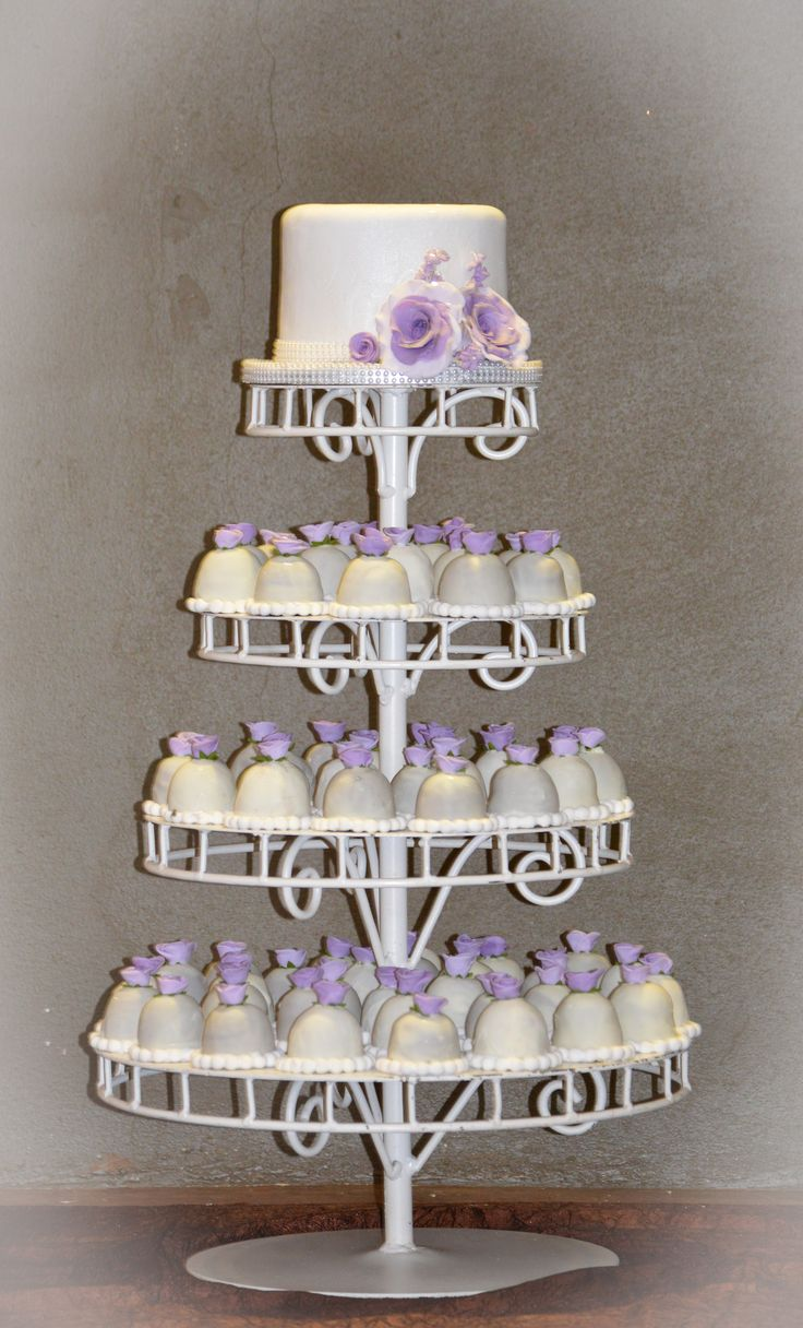 Sweetie pie cake, cute sweetie pies dipped in white chocolate and decorated with a sweet little edible purple Rose and finished off with edible pearls. Cutting cake with purple fondant roses and pearl details
