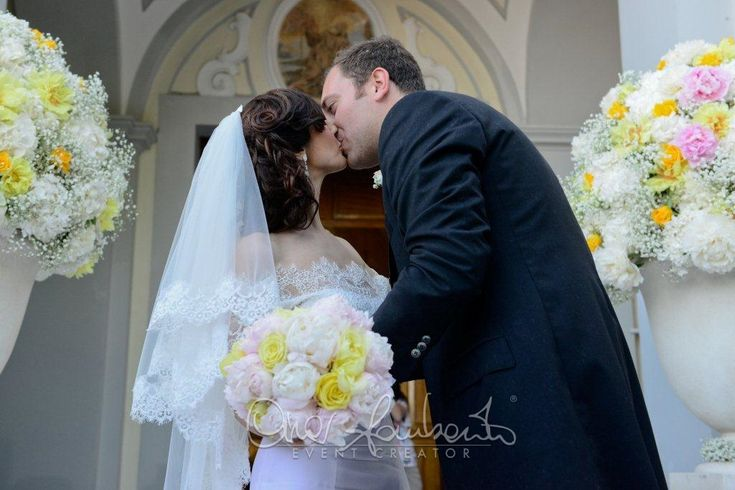 Bacio degli sposi tra nuvole di gypsophyla, rose e peonie gialle