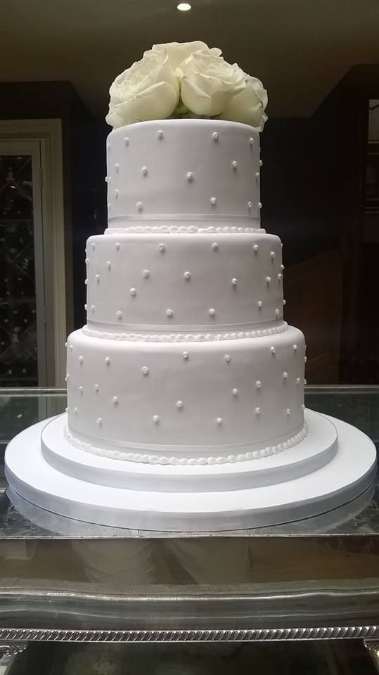 """Congratulations to Amy and Ian who got married last month at Lower Slaughter Manor!  This cake is made of:  6"""" Round classic vanilla cake layered with strawberry jam and vanilla butter cream 8"""" Round classic vanilla cake layered with strawberry jam and vanilla butter cream 10"""" Round moist carrot cake layered with vanilla butter cream  #cake #weddingcake #vanilla #buttercream # strawberry #jam #icing"""