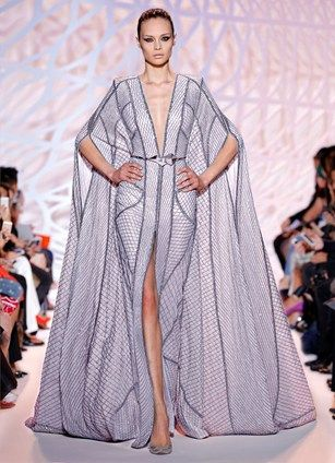 ZUHAIR MURAD - Art Deco-inspired beaded sheer caftan with strong shoulders and belted waist in silver.