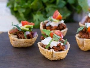 Mini Taco Bites are a fun and colorful party food that will be gobbled up at your next party. A ground beef/refried bean filling is covered with your choice of toppings.