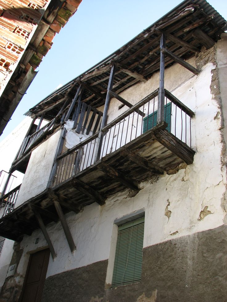 Clásico balcón voladizo apuntalado con vigas de madera y alero en el tejado para protegerlo de las lluvias.