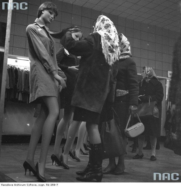 """Klientka oglądająca odzież damską z kolekcji """"Przekroju"""" w salonie mody na VI piętrze. Widoczne manekiny ustawione w rzędzie."""
