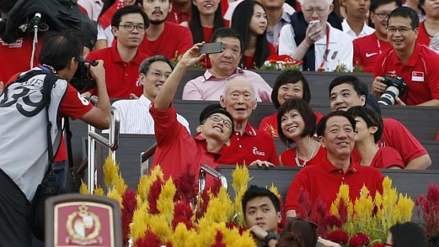 Singapore National Day Parade 2014: (From left) Minister of State for Trade and Industry Teo Ser Luck snaps a selfie with former prime minister Lee Kuan Yew as MP Lee Bee Wah, Senior Minister of State for Health Amy Khor, Senior Minister of State in the Prime Minister's Office Heng Chee How and Senior Minister of State for Education Indranee Rajah (partially hidden by Deputy Prime Minister Teo Chee Hean) look on. http://www.straitstimes.com/ndp2014 Photo: Kevin Lim/The Straits Times