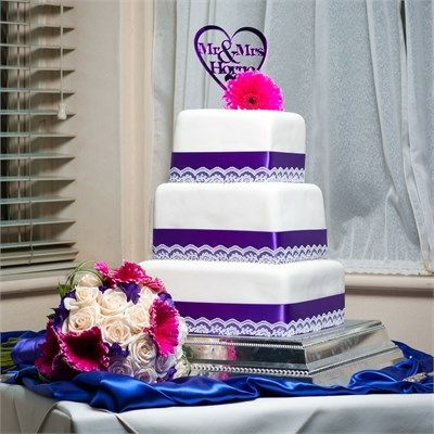 Sarah's clever mother made the 3 tier, square wedding cake that the newlywed couple cut through during their evening reception. The cake featured purple ribbon and lace that had been taken from Sarah's mother's wedding dress, and a bespoke cake topper with Mr
