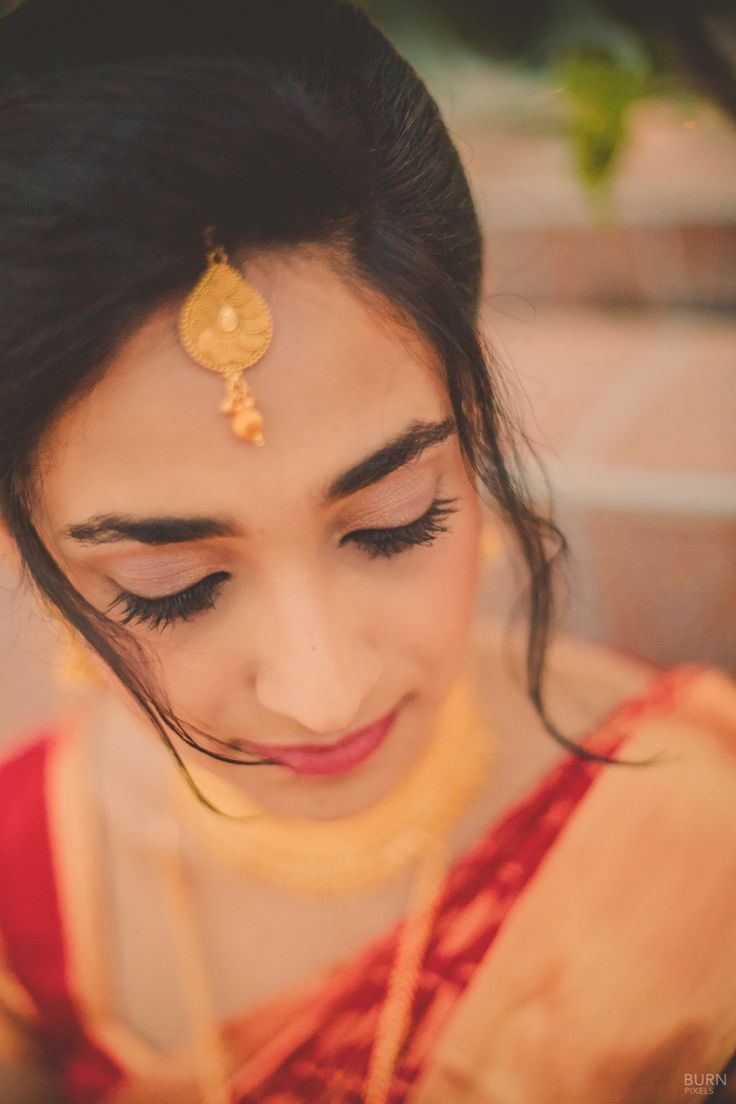 Bride wearing minimal traditional makeup with peach pink shaded lips.
