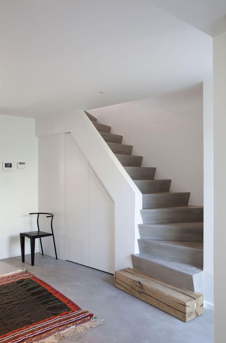 JV n°54 - Un kilim marocain coloré de la boutique Items pour réchauffer le lieu. Sous l'escalier en béton, un placard peint en blanc, dans un souci de dépouillement. (C) : Bieke Claessens