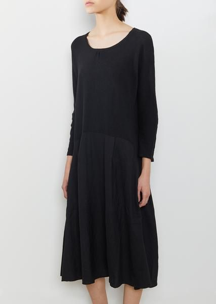 Black long-sleeve tent dress in wool with an arched seam for a dropped waist. Relaxed fit. Yoked seam at back.Gathered pleats along the chest and skirt. Color: