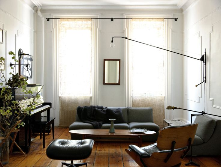Living room with an upright piano, plant, Eames chair, grey sofas.