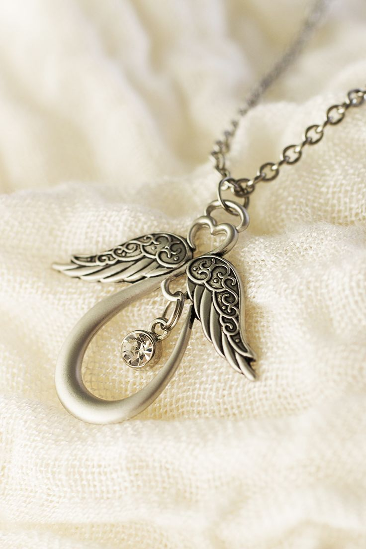 "In the face of life's toughest challenges, a little faith goes a long way. Our brushed silver-tone pendant shares heavenly inspiration. The angelic heart silhouette bears a crystal, the flourished wings etched with the message ""Angels are closer than you think™"" on the reverse side."
