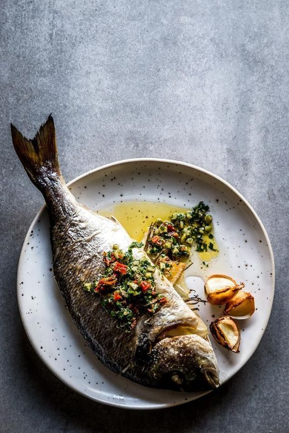 An easy and healthy baked fish recipe, this whole fish is a flavorful and simple weeknight dinner recipe. Make it with your favorite whole white fish, such as sea bream, sea bass or branzino. Stuffed with herbs, lemon and garlic butter and served with a briny salsa made from capers, sun-dried tomatoes and green olives, it is a Mediterranean feast. The best clean eating meal, easily adaptable with clarified butter for paleo or whole 30 diets, too.