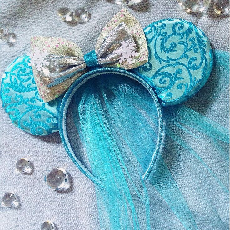 Frozen+inspired+mouse+ears+with+beautiful+icy+blue+veil+and+snowflake+embellished+sparkly+bow.+Headband+fits+both+children+and+adults+comfortably.