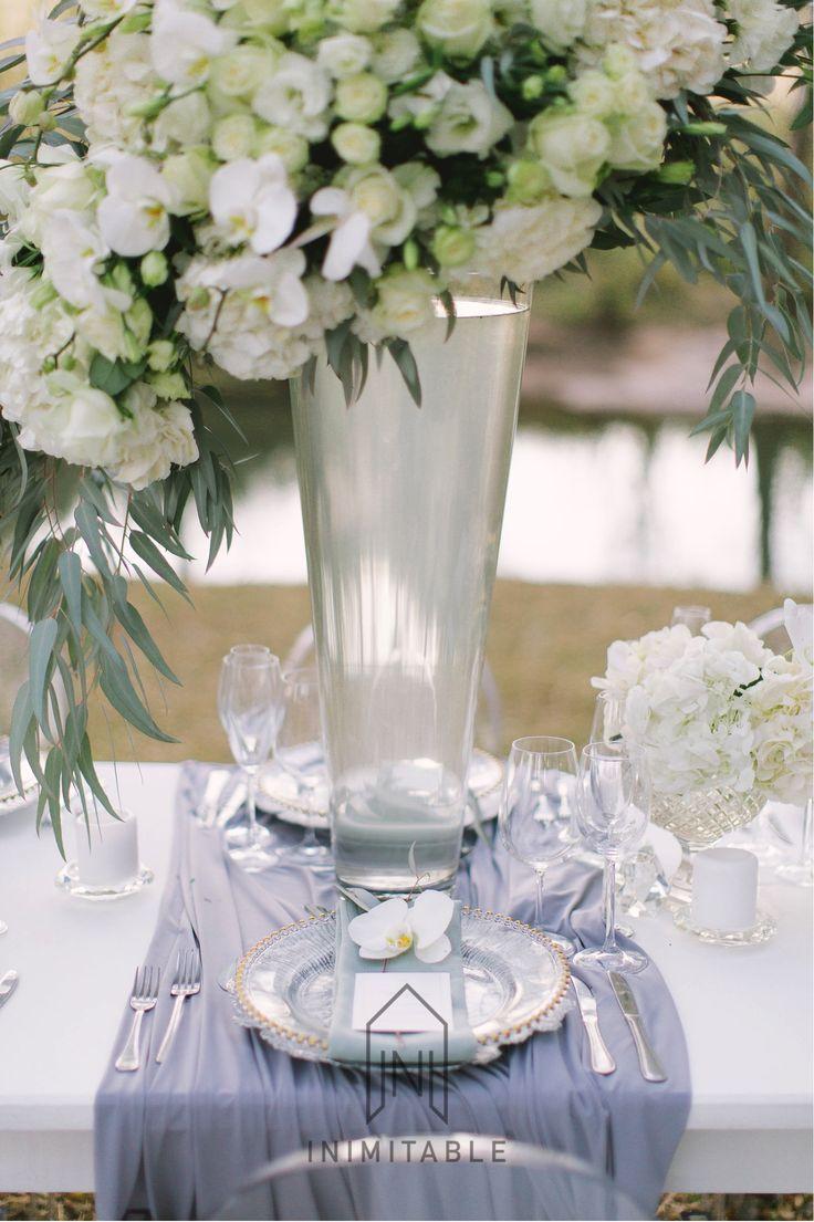 Inimitable Wedding Venue. Photography: @genevieve_fundaro  Hair and Make-up: @refinerythe  Dress: @calegrabridal  Floral Design: @zavionkotzeeventscompany  Venue: @inimitable_wv   #luxury #luxuryvenue #luxeweddings #luxewedding #flowerwall #allwhite #bride #bridal #floraldesign #bouquet. White and green flowers, gold under plates, grey, orchids, roses, elegant wedding table. floral art, wedding day, wedding experience, best wedding ever