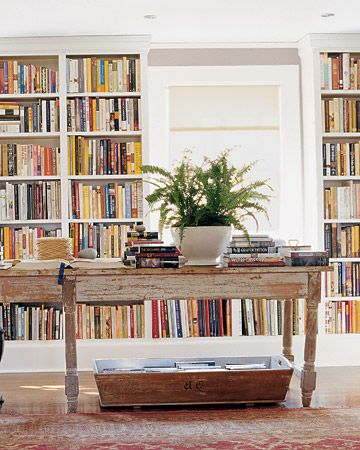 one wall of living room is mini-library; Love the long library table and dough trough beneath