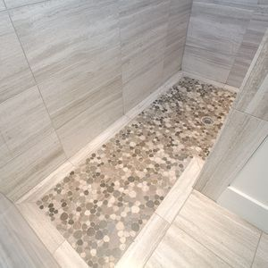 This client was not fond of glass-enclosed showers, so this walk-in design actually wraps around the corner, making a glass door and/or wall unnecessary. The floor of the shower is tiled with a stone made to look like a pebble floor, but smooth in texture so it is easy on your feet.