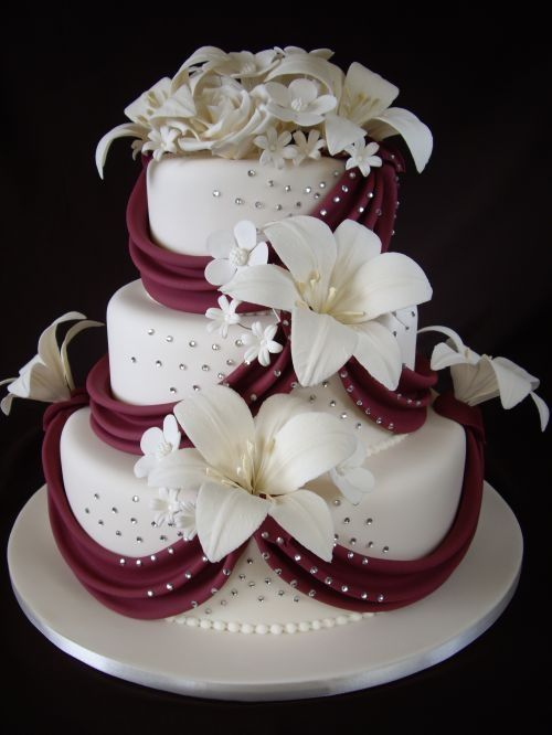 3 tier cake covered in ivory sugarpaste and topped with sugar flowers and burgundy red draping