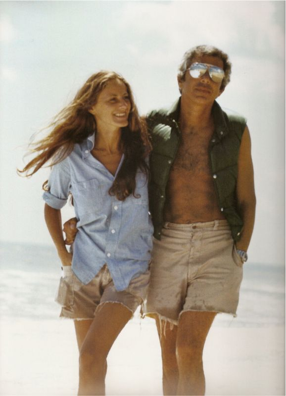 """Photo of Ricky and Ralph Lauren walking on the beach in Amagansett, Long Island, 1977 by Les Goldberg.    """"I love to shop with Ricky. Not long after we met, we went to an old riding apparel store and I bought her a boy's tweed hacking jacket. It fit her beautifully, and everyone asked about it. That's when I decided to do women's clothes. I liked her style.""""—Ralph Lauren in an excerpt from Ralph Lauren, 2007."""
