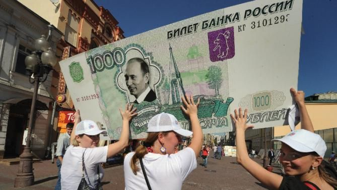 RUSSIAN RUBLE DROPS PAST 60 PER DOLLAR Supporters of Vladimir Putin carry a mock 1,000 ruble banknote in Moscow