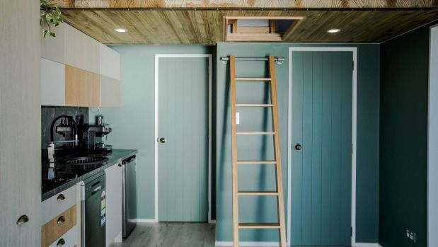 A ladder near the kitchen leads up to the trap door opening to the loft bedroom.
