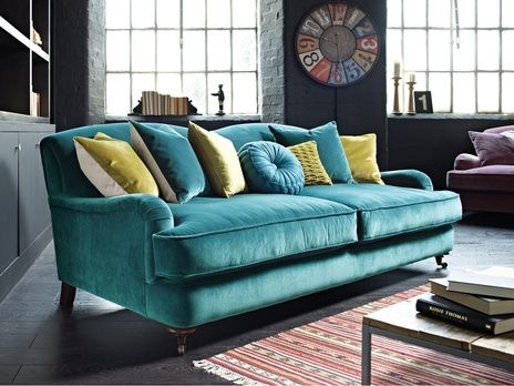 This sofa covered in peacock-colored velvet stands out in a subdued gray family room.