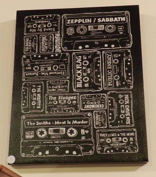 This Original wall art depicts cassette tapes with band names such as Nick Cave, Public Enemy, Zepplin and The Misfits, just to name a few. The Artwork measures
