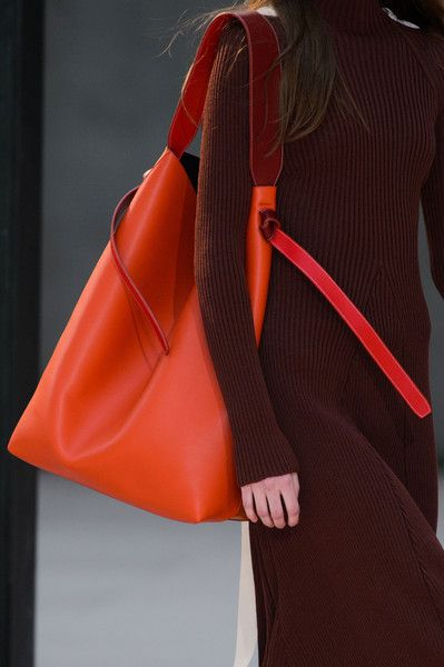 Céline at Paris Fall 2015 (Details). I typically hate orange, but the intense hue of the bag and its sharp contrast against the burgundy dress are incredible.