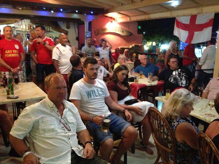 Greece. Corfu. Friendly English football fans in taverna