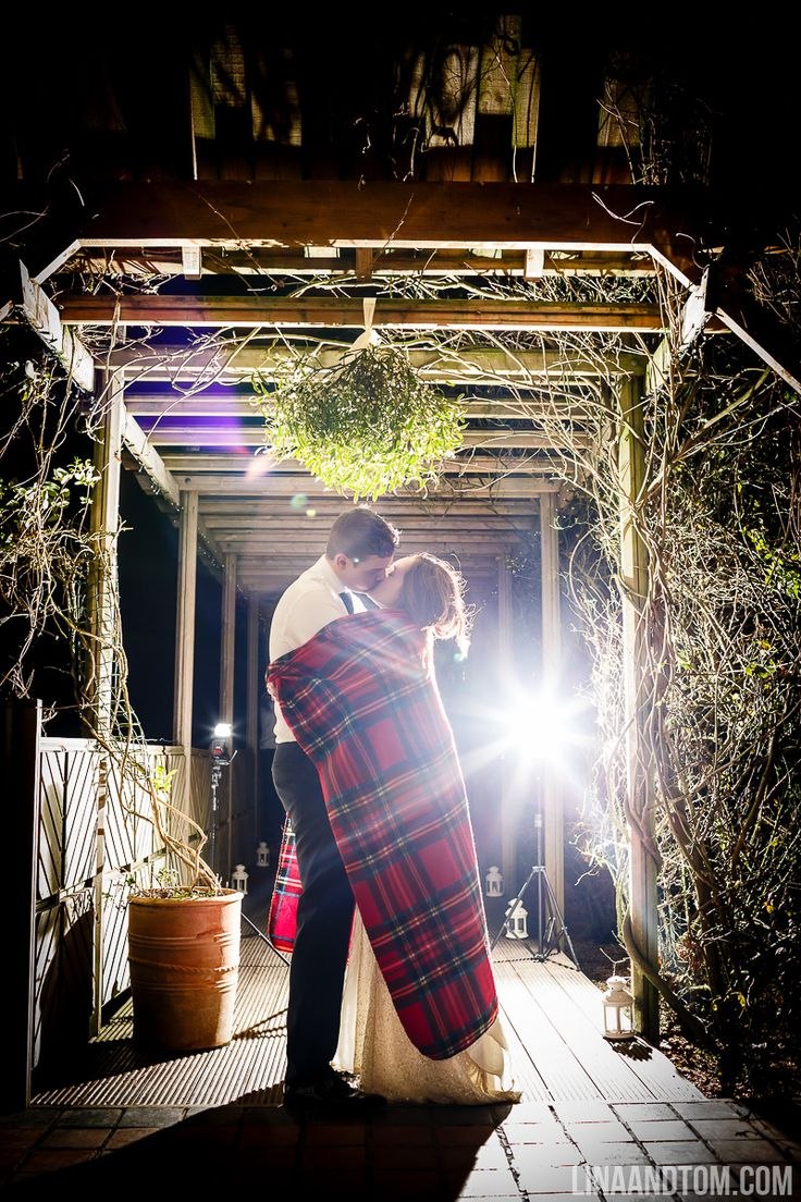 Cuddle up! A kiss under the mistletoe for the newlyweds.  Sophie and James' winter wedding photographed by Lina and Tom.