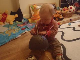 Threading straws through a colander.