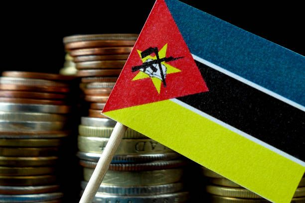 mozambique flag waving with stack of money coins macro